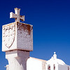 Stone cross with the Portuguese national emblem and Nossa Senhora da Graça church, fortress of the town of Sagres, municipality of Vila do Bispo, district of Faro, region of Algarve, southwestern Portugal