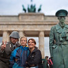 Tourists posing with street actors disguissed as former GDR soldiers in front of the Branderburg Gate, Berlin, Germany