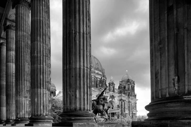 Black and white image of the Berliner Dom (Cathedral) as seen from behind the columns of the Altes Museum portico, Berlin, Germany