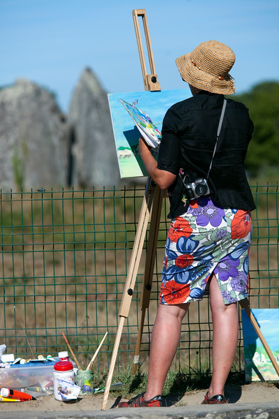 Woman painting at the megalithic alignment of Kermario, town of Carnac, departament of Morbihan, Brittany, France