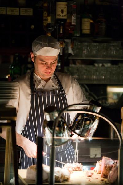 O'Neills Victorian Pub employee cutting meat, Dublin, Ireland