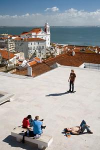 Young people sunbathing at Santa Luzia viewpoint, Lisbon, Portugal