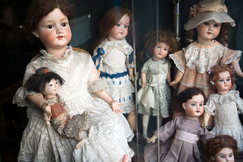 Vintage porcelain dolls exposed on a shop window, Calçada do Combro, Lisbon