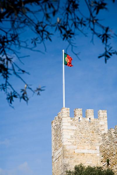 The Portuguese flag fluttering on the top of Saint George castle, Lisbon