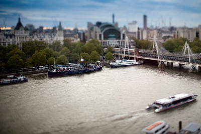 Aerial view of ships and boats on the Thames river with the Hungerford bridge on the background, London, England, United Kingdom.Tilted lens used for shallow depth of field.