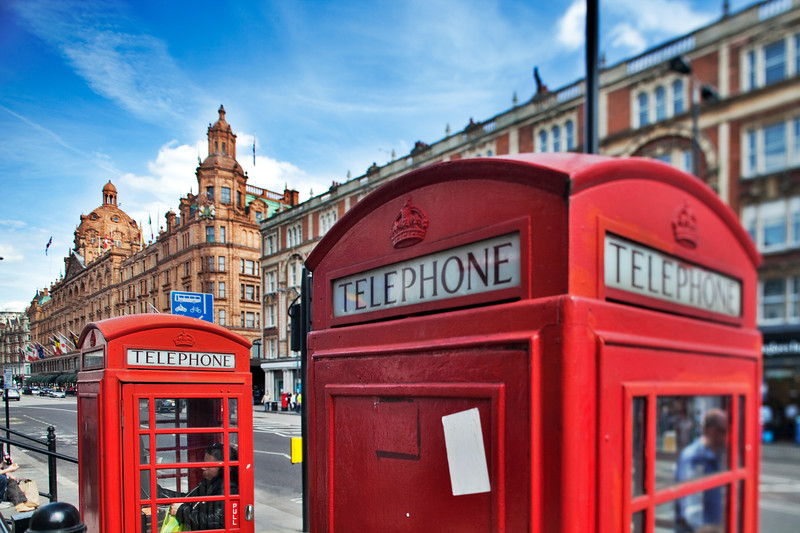 Typical red telephone boxes on Brompton Road with Harrods building on the background. London, England, United Kingdom