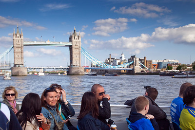 Group of tourists on a boat in front of Tower Bridge,  London, England, United Kingdom