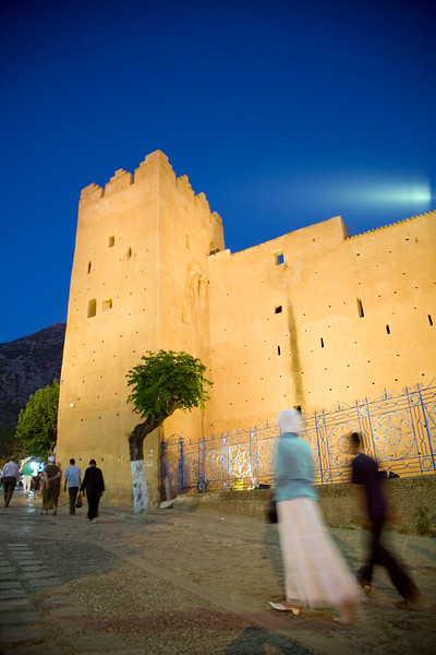 People walking by the Kasbah at dusk, town of Chefchaouen, northern Morocco, Africa