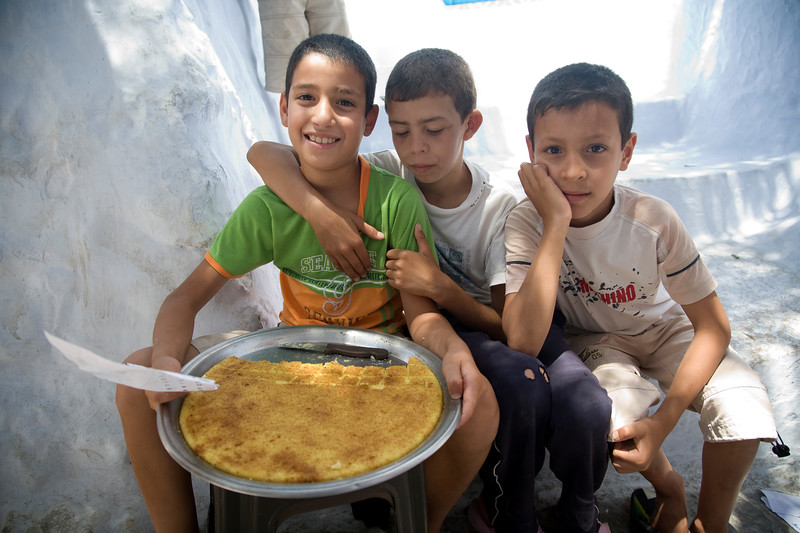 Kids selling cakes on the street, town of Chefchaouen, northern Morocco, Africa