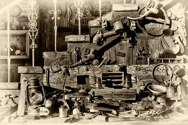 Bench full of vintage tools below the stairs.