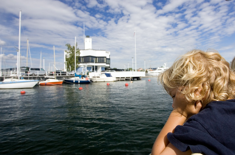Typical nordic kid looking at the sea from a recreation boat.