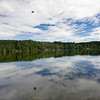 Idyllic images of Sognsvann lake, Oslo. An airplane on the sky is reflected on the water.