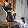 Afro-American visitor posing beside Saint Peter statue, Saint Peter's basilica, Vatican