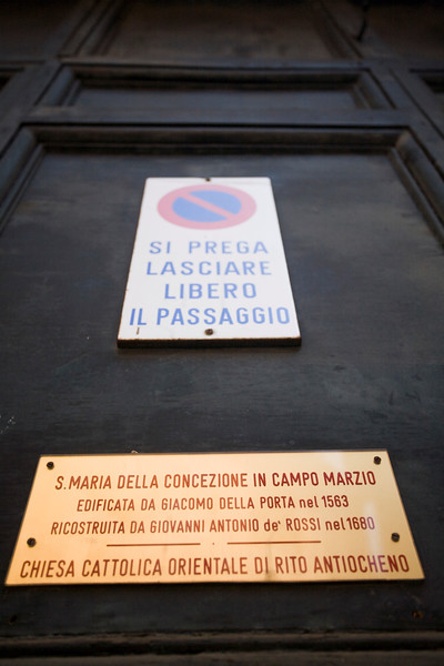 Traffic and information signs on the door of Santa Maria della Concezione in Campo Marzio church, Rome