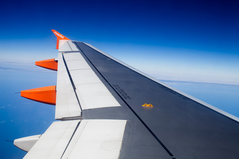 Wing of an airplane belonging to EasyJet flying over Portugal