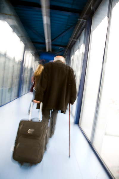Old man drawing a roller suitcase through an airport corridor
