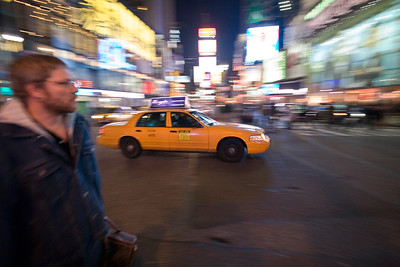 Young man and yellow cab in Times Square, NYC, USA