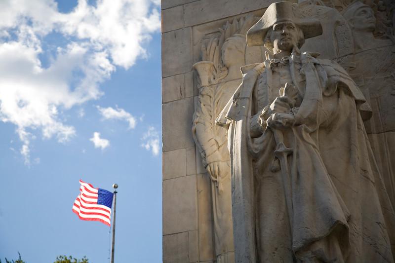 Detail of a sculpture of George Washington from Washington Square Arch, NYC, with the American flag flying on the background.