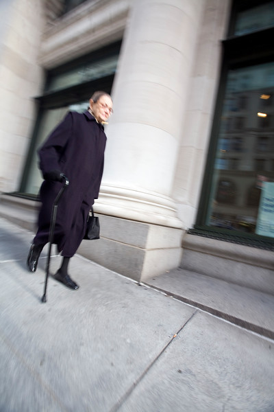 Old lady in black walking down the 5th Avenue, NYC; USA