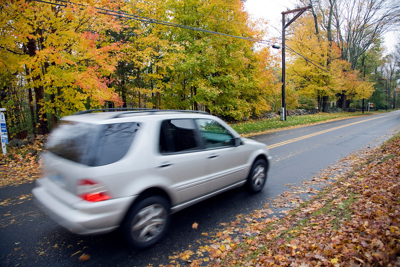 Four by four vehicle on a secondary road in the fall, Connecticut, USA