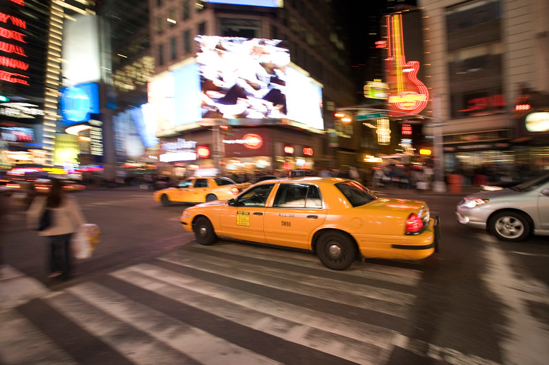 Panning shot of a yellow cab, Times Square, NYC, USA.