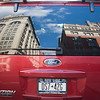 Buildings of 5th Av. reflected on the rear window of a Ford automobile
