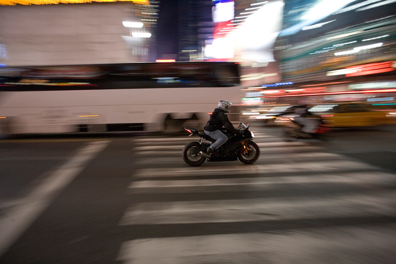 Panning shot of a man riding a motorbike in Times Square, New York, USA
