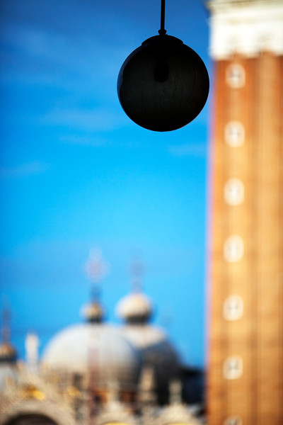Street lamp on Piazza San Marco with the Campanile and the Basilica blurred on the background