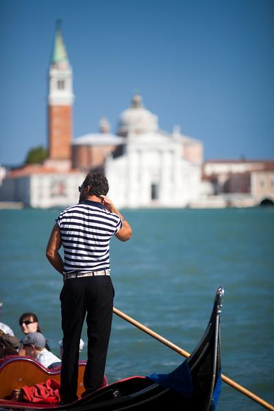 Gondolier at work in front of San Giorgio Maggiore, Venice, Italy