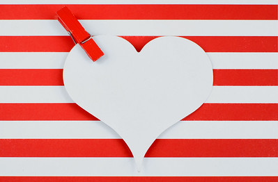 Cheerful red and white horizontal stripes form the background. A red clothespin is at the corner of a white, heart-shaped cutout. Copy space.