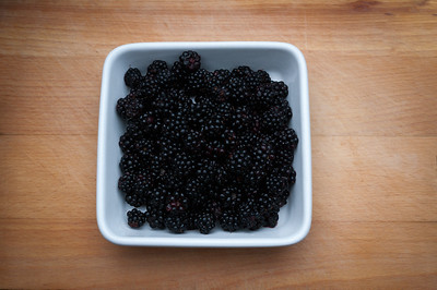 Blackberries in white bowl.