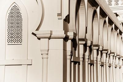 Horseshoe arches and a lattice window in two facades of the Shaikh Isa bin Ali mosque, Muharraq, Bahrain.