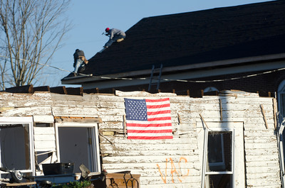 HENRYVILLE, IN, USA - MARCH 10, 2012 - Workers fix the roof of a church while an American flag is hanging on the wreckage of a home damaged during an EF4 tornado that struck Henryville, Indiana, USA, on March 2, 2012.