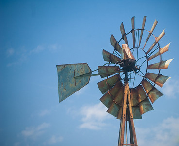 A weathered windmill against a blue sky.