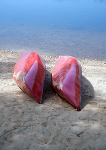 Two red canoes on the side of a pond in Canada