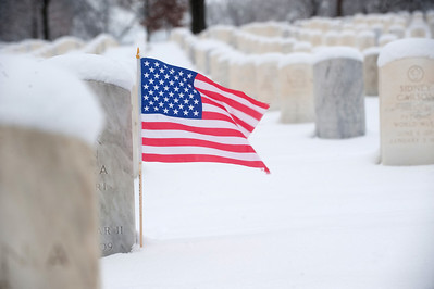 United States flag at the grave stone of a US solider in Jefferson Barracks National Cemetery near St. Louis Missouri. Photos taken after a winter storm.