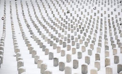 Snowfall blankets gravesites of United States military veterans in Jefferson Barracks National Cemetery