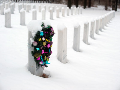 Christmas wreath hanging on a grave stone in Jefferson Barracks National Cemetery near St. Louis, Missouri.