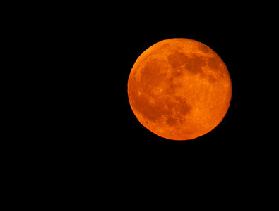 Reddish orange tint on the full moon as it rises in the night sky