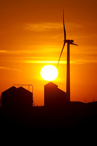 Agricutural silos of grain operation and turbines from a wind farm silhouetted by setting sun