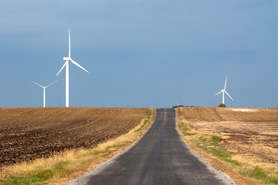 A country gravel road leading to large wind turbine on a windfarm