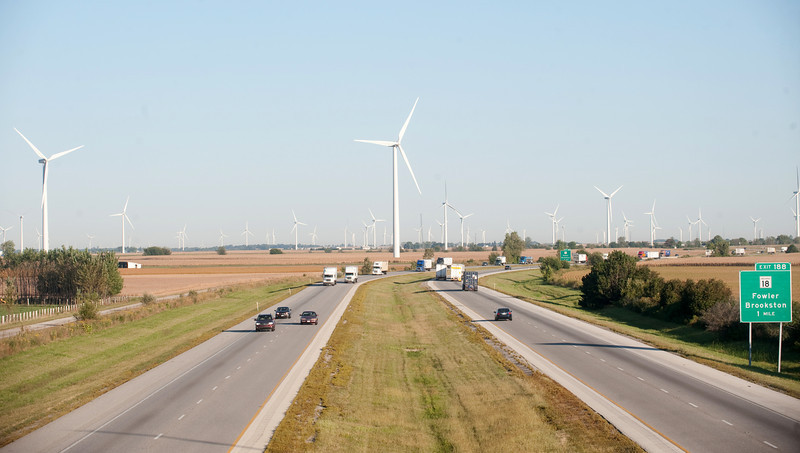 Traffic moves along an interstate highway with wind turbines in the background