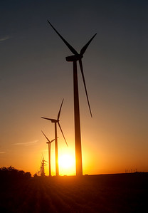 A wind turbine is silhouetted by the setting sun
