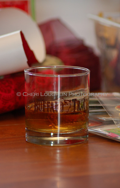 Buffalo Trace glass with bourbon on the rocks, holiday wrapping paper in the background.