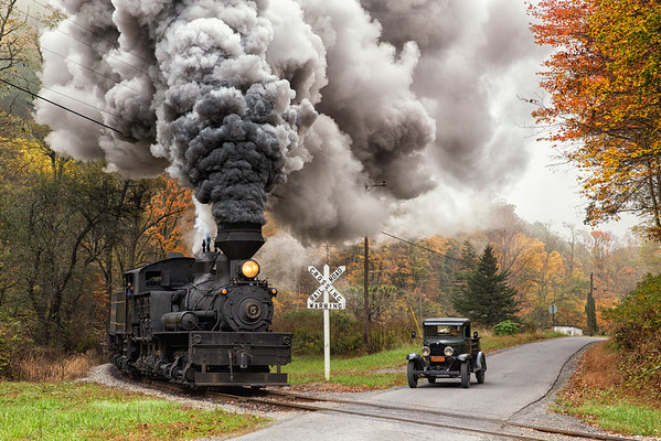 With Engineer Dirk Caloccia at the throttle, Shay no. 5 hustles through Back Mountain Road crossing, as a 1930 Pocahontas Supply Co. Chevy, driven by Bert Krieps, pauses for the train.