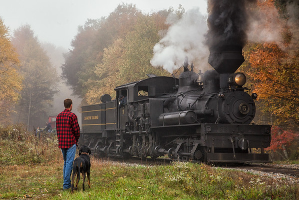 Cass Scenic Railroad State Park Assistant Superintendent Josh Feather waves at Shay No. 5 as his dog Otis looks on as the train passes through Shalimar Farm.