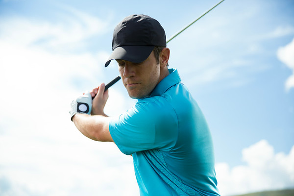 a male golfer swinging a golf club