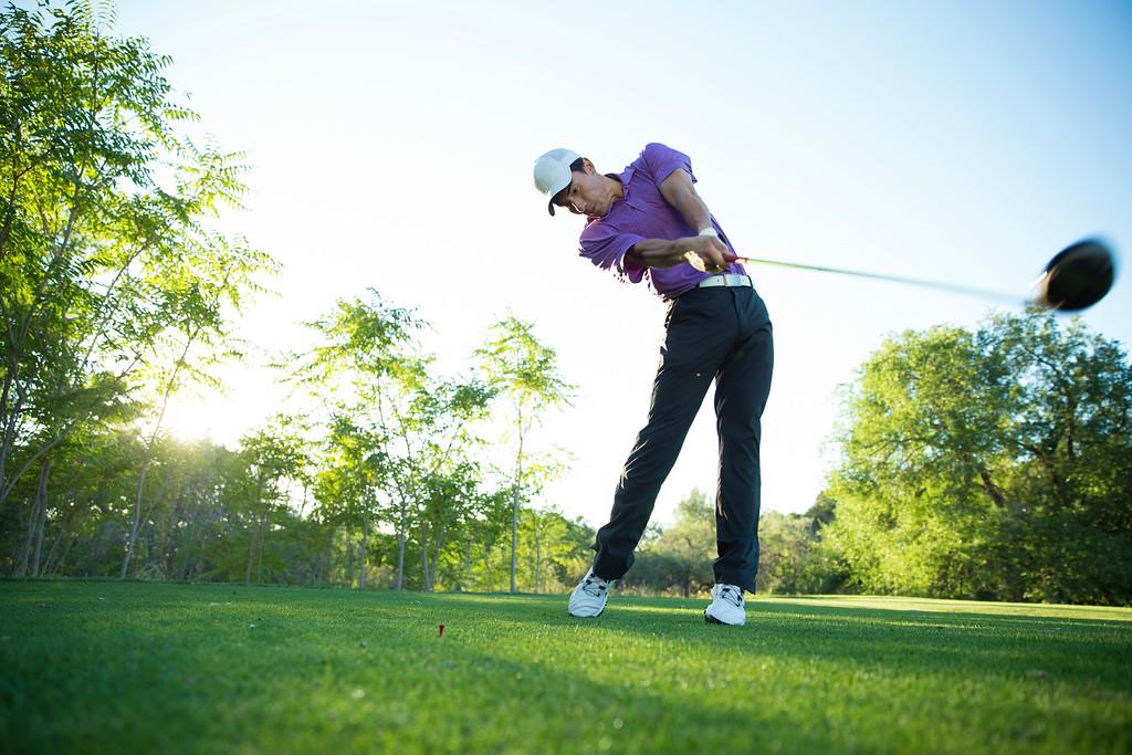 a male golfer swinging a golf club