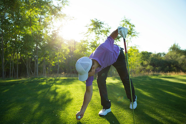 a male golfer getting ready to tee off on the golf course