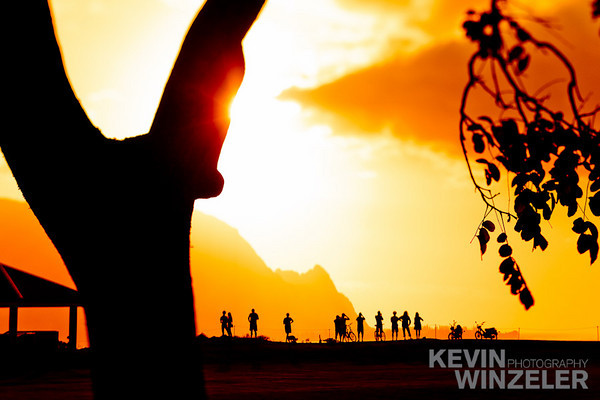 visitors relish the epic sunset over the coast of Napali and the Hanalei bay. Location: Kauai, Hawaii